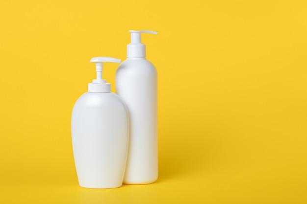 Sapone liquido in un flacone. set di bottiglie di plastica con dispenser su una parete gialla. copia spazio, posto vuoto per il testo. lozione pompa. crema idratante per corpo e viso. concetto di igiene personale.
