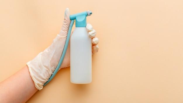 Spray liquido in mano femminile hardware cosmetologia idrodermoabrasione e dispositivi di sollevamento dermatologia cosmetologia cosmetici combinare strumenti per la cura della pelle del viso salute lungo banner web sfondo beige