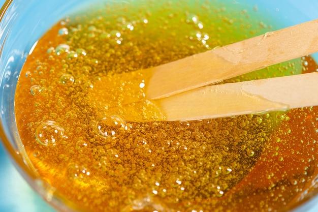 Pasta liquida gialla per zuccherare e bastoncini su blu. depilazione e concetto di depilazione.