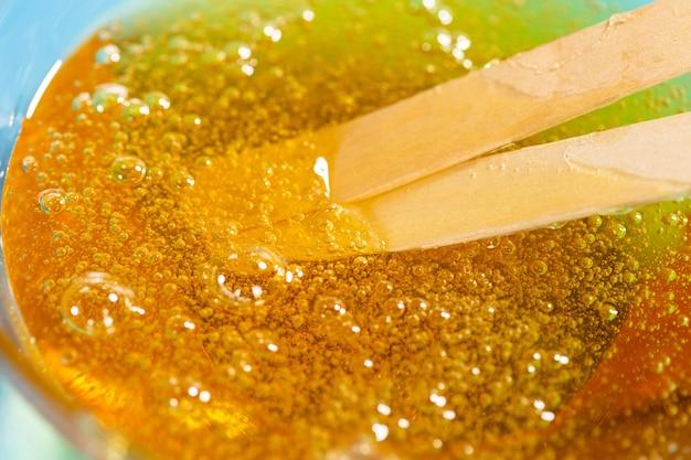 Cera liquida gialla o pasta di zucchero per la depilazione e bastoncini su sfondo blu. il concetto di