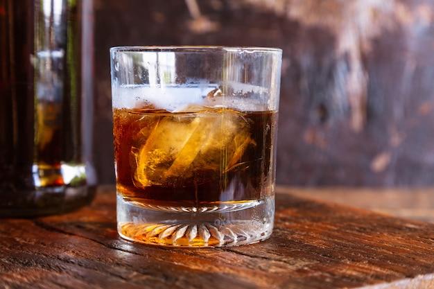 Bicchiere da liquore e decanter sul tavolo di legno