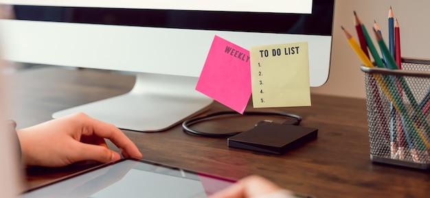 To do list concept, mano utilizzando tavoletta digitale e computer con pianificazione della nota di carta.