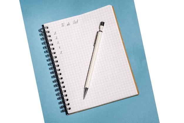 Elenco delle cose da fare in taccuino con penna su sfondo blu isolato su bianco. luogo di lavoro e concetto di pianificazione, vista dall'alto.