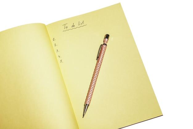 Elenco delle cose da fare nel taccuino giallo con penna rosa isolato su bianco. luogo di lavoro e concetto di pianificazione, vista dall'alto.