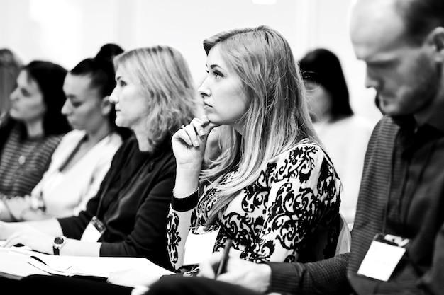 Gli ascoltatori prendono appunti sui quaderni, seduti nella sala conferenze. foto in bianco e nero
