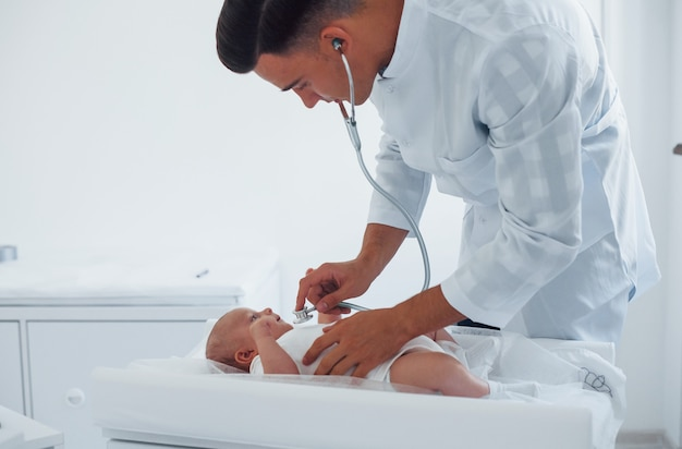 Ascolto utilizzando lo stetoscopio. il giovane pediatra è con il piccolo bambino nella clinica durante il giorno.