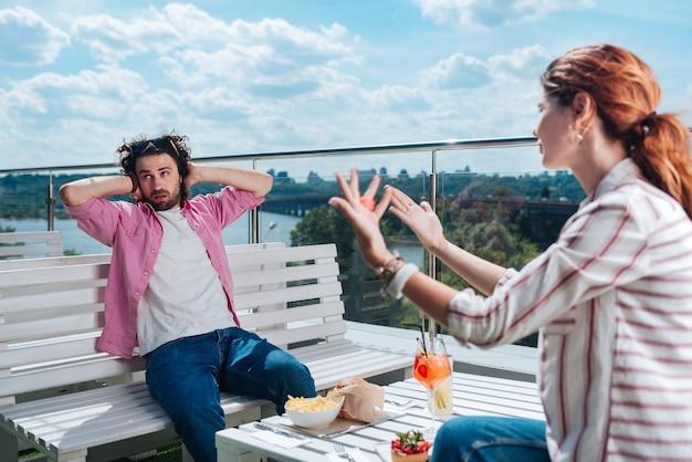 Non ascoltando. bell'uomo riccio che finge di non ascoltare la sua ragazza mentre si cena romantica sulla terrazza