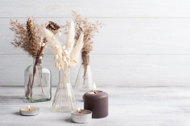 Candele aromatiche accese e fiori secchi su fondo rustico. disposizione spa in stile monocromatico