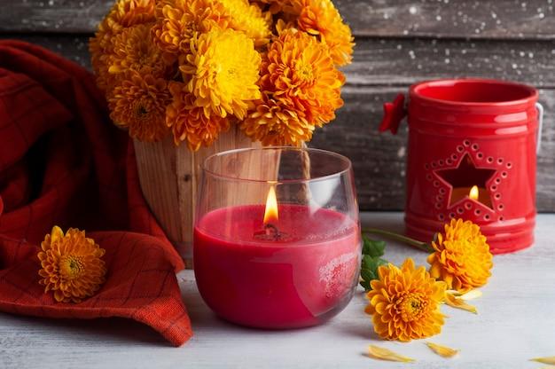 Aroma acceso candela rossa e fiori d'arancio su fondo rustico. biglietto di auguri con copia spazio per il testo