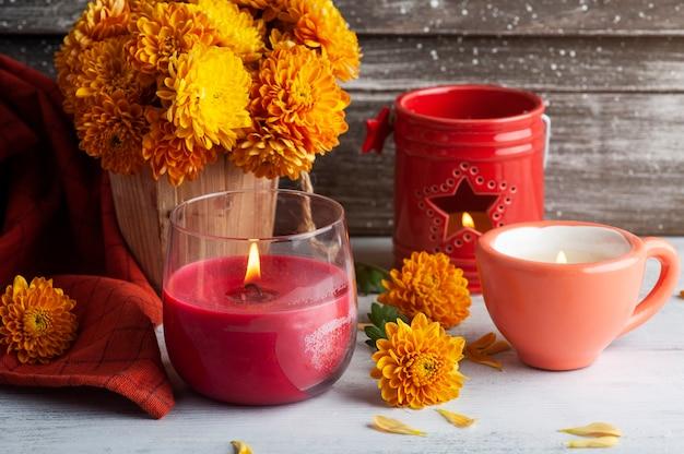 Candela rossa aromatica accesa e fiori d'arancio