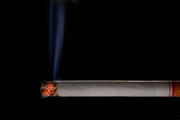 Sigaretta accesa e bruciante con fumo su fondo nero