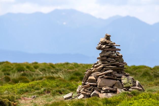 Illuminato dal sole estivo luminoso pietre irregolari di montagna accatastate ed equilibrate come un mucchio di piramide sulla valle erbosa verde sul cielo blu chiaro spazio bianco copia. turismo. concetto di viaggio e punto di riferimento.