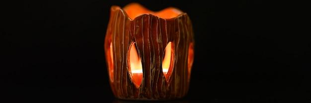 La candela accesa brucia all'interno del candeliere su uno sfondo nero. bella luce del fuoco dalle feritoie di un candelabro in argilla. banner