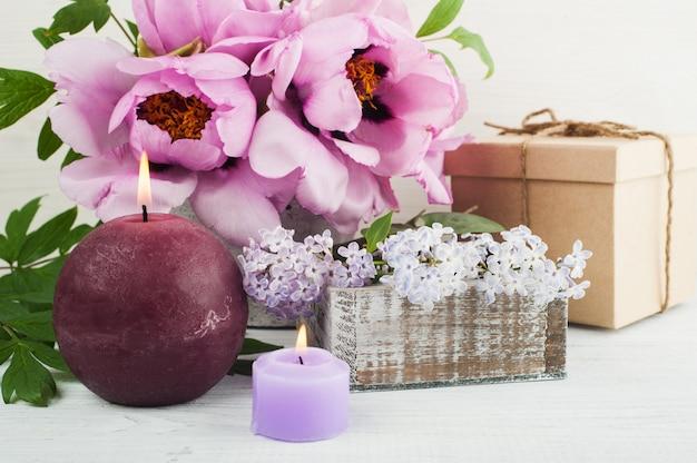 Candele accese, peonie e fiori lilla