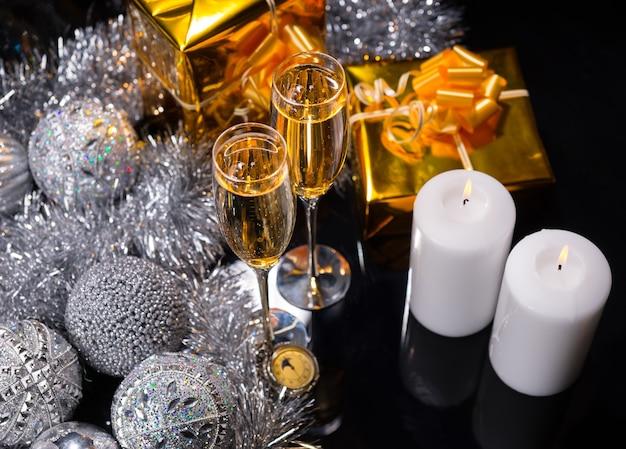Candele accese con bicchieri di champagne festivo
