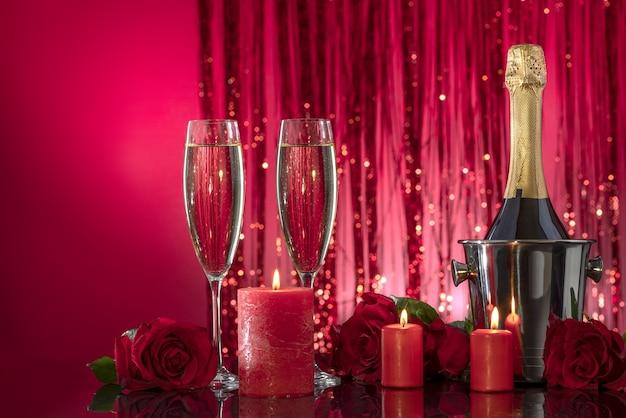Candele rosse accese in candelieri trasparenti illuminano una bottiglia e bicchieri di lusso