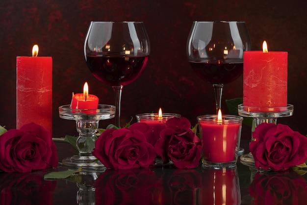 Candele rosse accese in candelieri trasparenti illuminano bicchieri di vino circondati da rose