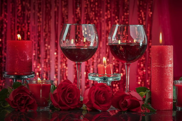 Candele rosse accese in candelieri trasparenti illuminano i bicchieri con il vino circondato
