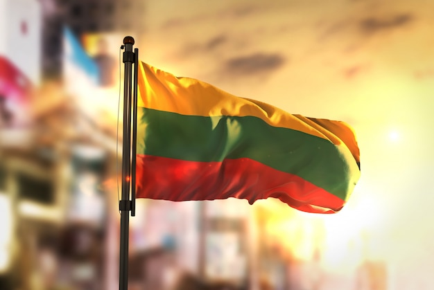 Bandiera della lituania contro la città sfocata di sfondo all'illuminazione di sunrise