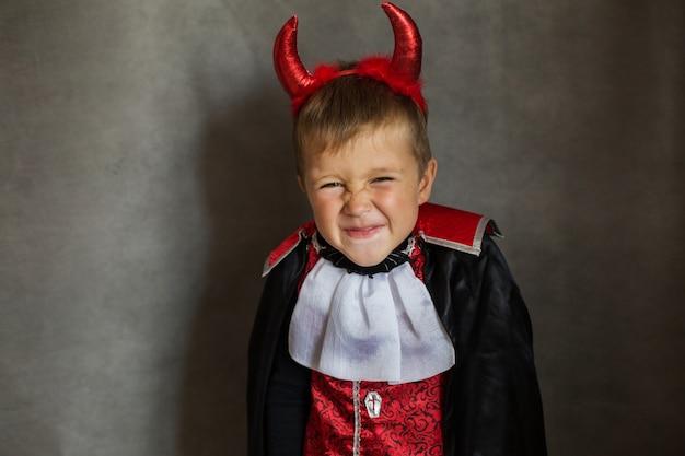 Piccolo ragazzo in costume da vampiro di halloween sul muro grigio