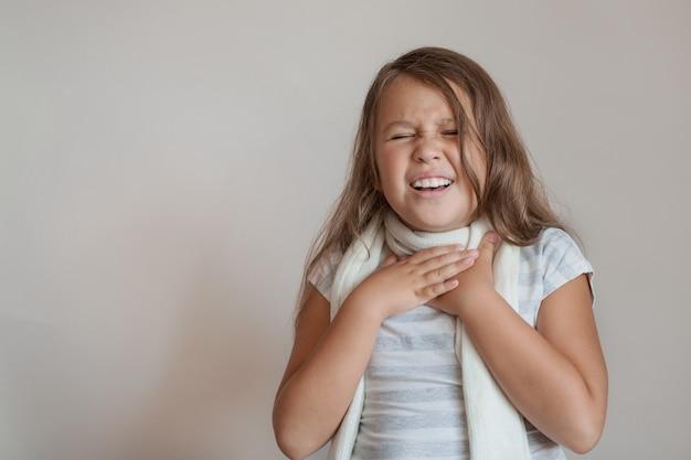 Piccola ragazza ha mal di gola con sciarpa bianca su grigio.