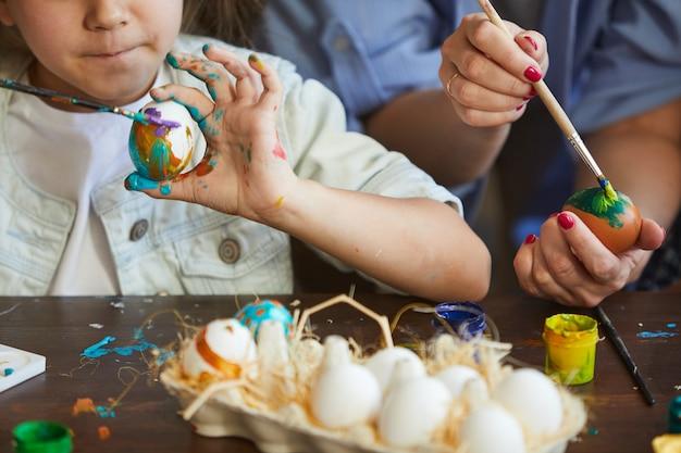 Primo piano delle uova di pasqua della pittura della ragazza di litte