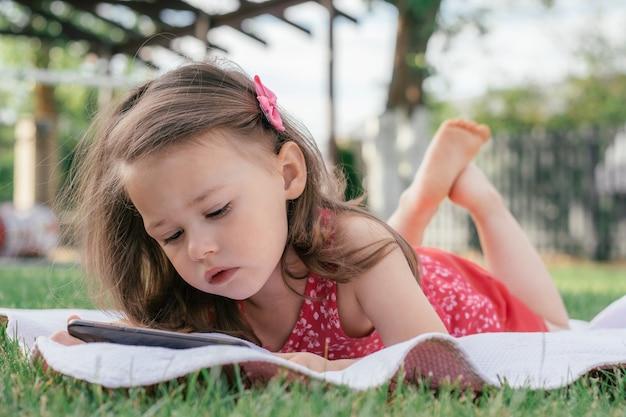 La piccola 3-4 ragazza in vestiti rossi si trova su una coperta sull'erba verde e guarda nel telefono cellulare. bambini, usando i gadget