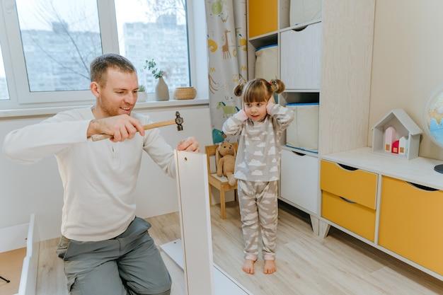 Bambina di 4 anni chiude le orecchie con le mani perché fa un forte rumore mentre suo padre usa il martello per riparare il cassetto del letto nella cameretta dei bambini.