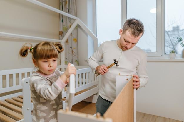 La bambina di 4 anni aiuta suo padre a montare o sistemare il cassetto del letto nella cameretta dei bambini.