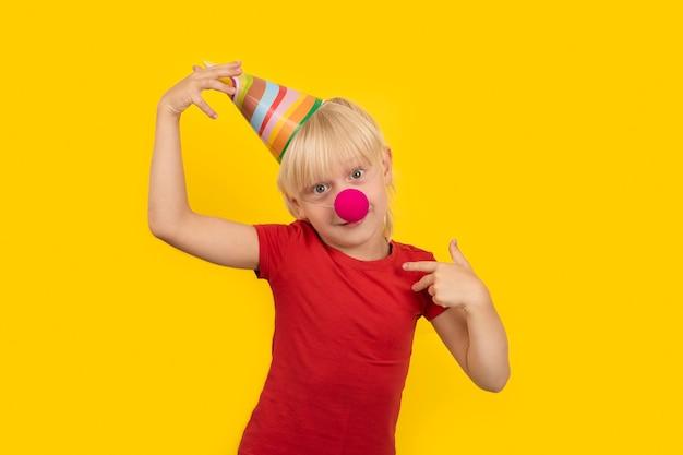 Piccolo ragazzo biondo di 5 anni che indossa cappello da festa e naso rosso da clown. festa di compleanno.