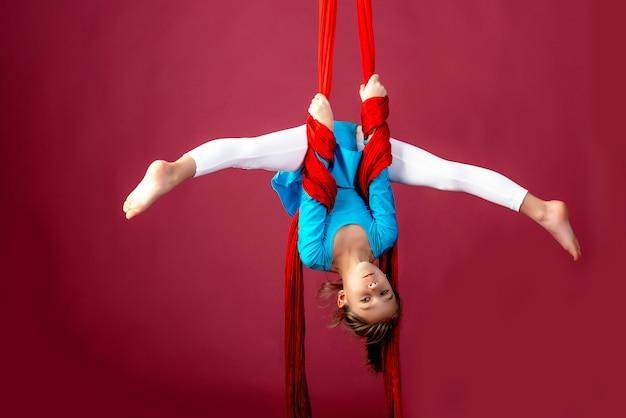 La piccola ragazza dell'acrobata che fa si divide nell'aria