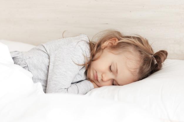 Piccola bambina adorabile in pigiama grigio occhi chiusi sdraiata a letto che dorme su un comodo cuscino e sotto una soffice coperta di cotone bianco, buona notte sogni d'oro