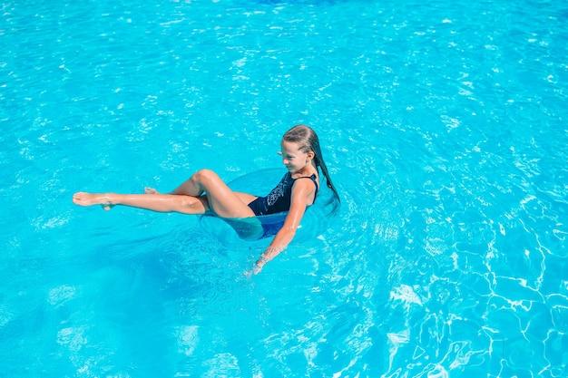 Piccola ragazza adorabile nella piscina all'aperto