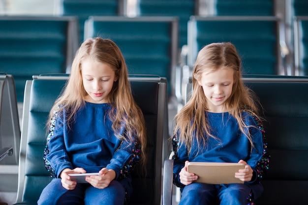 Piccole ragazze adorabili nell'imbarco aspettante dell'aeroporto che gioca con il computer portatile