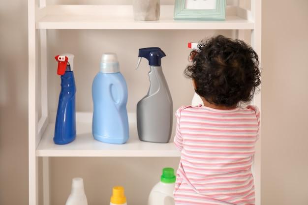 Piccolo bambino afro-americano che gioca con i liquidi di lavaggio a casa. bambino in pericolo