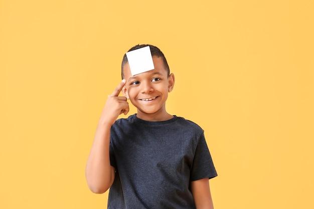 Piccolo ragazzo afro-americano con carta per appunti in bianco sulla fronte contro la superficie del colore