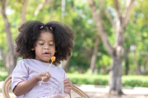 Un po' di capelli ricci afroamericani si divertono a mangiare con la salsiccia