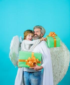 Il piccolo angelo fa un regalo al padre padre felice in costume da angelo con il figlio piccolo che l'angelo tiene presente