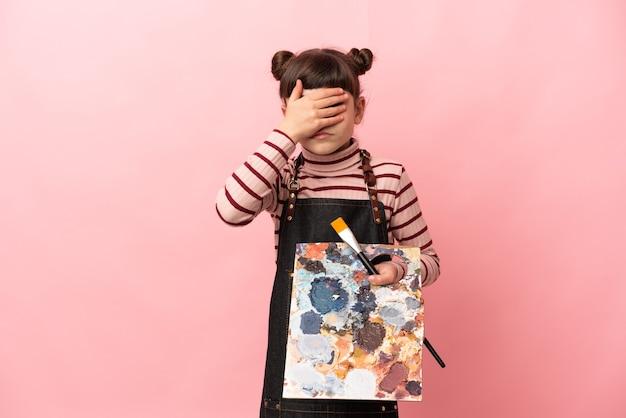 Piccola ragazza dell'artista che tiene una tavolozza isolata su fondo rosa che copre gli occhi con le mani. non voglio vedere qualcosa