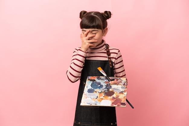 Piccola ragazza dell'artista che tiene una tavolozza isolata sulla risata rosa del fondo