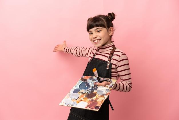 Piccola ragazza dell'artista che tiene una tavolozza isolata sulla parete rosa che estende le mani a lato per invitare a venire