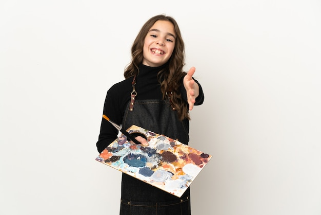 Piccola ragazza dell'artista che tiene una tavolozza isolata sulla parete bianca che stringe la mano per chiudere un buon affare