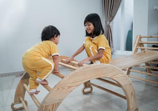 Piccolo bambino asiatico arrampicata pikler triangolo giocattoli che accompagnano la sua sorella maggiore
