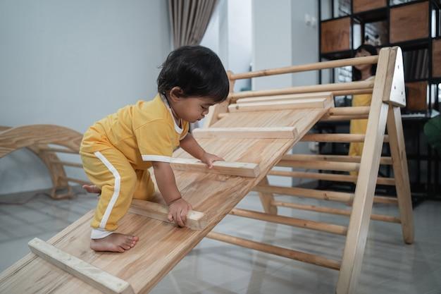Piccolo bambino asiatico che striscia sui giocattoli del triangolo di pikler sullo sfondo del soggiorno