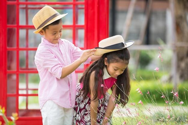 Il piccoli ragazzo e ragazza asiatici godono di di giocare nel concetto del giardino, del biglietto di s. valentino o di amore