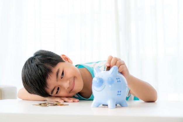 Il piccolo ragazzo asiatico inserisce una moneta nel porcellino salvadanaio blu in tavola bianca al salone a casa per il risparmio del bambino.