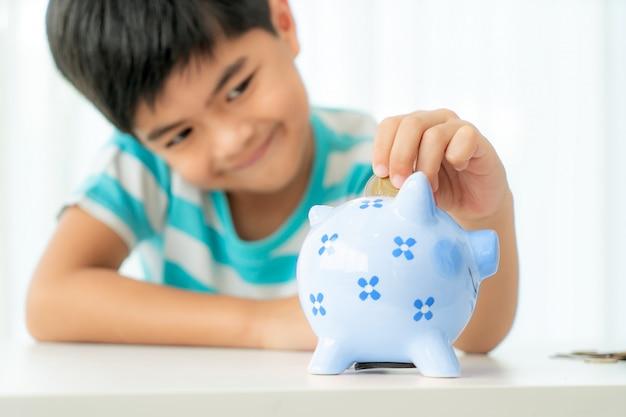 Il piccolo ragazzo asiatico inserisce una moneta in un salvadanaio blu