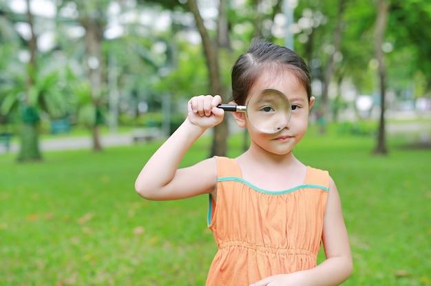 Piccola ragazza asiatica del bambino che guarda attraverso il vetro di ingrandimento sopra ad erba all'aperto.