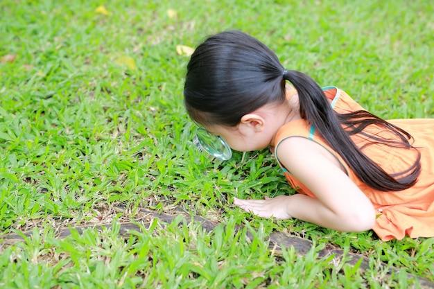 Piccola ragazza asiatica del bambino con la lente d'ingrandimento sul giardino dell'erba verde. natura di primo piano come ricercatore.