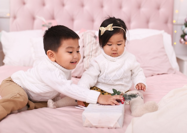 Piccoli bambini asiatici ragazzo e una donna in maglioni si aprono e giocano mentre erano seduti sul letto a casa